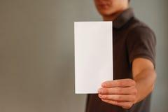 Άτομο που παρουσιάζει κενό άσπρο βιβλιάριο φυλλάδιων ιπτάμενων Presenta φυλλάδιων Στοκ Φωτογραφία