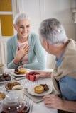 Άτομο που παρουσιάζει να εκπλήξει το δώρο στη σύζυγό του κατά τη διάρκεια του προγεύματος στο σπίτι Στοκ εικόνα με δικαίωμα ελεύθερης χρήσης
