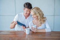 Άτομο που παρουσιάζει στη σύζυγό του κάτι σε μια ταμπλέτα Στοκ Εικόνες