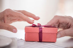Άτομο που παρουσιάζει το δώρο στο κιβώτιο με την κορδέλλα στη σύζυγό του Στοκ Φωτογραφία