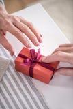 Άτομο που παρουσιάζει το δώρο στο κιβώτιο με την κορδέλλα στη σύζυγό του Στοκ εικόνες με δικαίωμα ελεύθερης χρήσης
