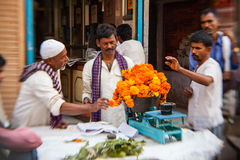 Άτομο που περνά κλωστή στις ζωηρόχρωμες γιρλάντες λουλουδιών στο Δελχί Στοκ Εικόνα