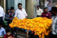 Άτομο που περνά κλωστή στις ζωηρόχρωμες γιρλάντες λουλουδιών στο Δελχί Στοκ εικόνες με δικαίωμα ελεύθερης χρήσης