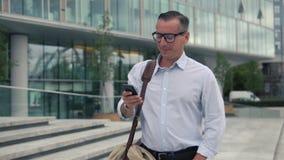 Άτομο που περπατά και που χρησιμοποιεί το smartphone απόθεμα βίντεο