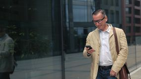 Άτομο που περπατά και που χρησιμοποιεί το smartphone φιλμ μικρού μήκους