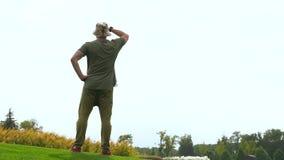 Άτομο που περπατά πέρα από την κοντή χλόη σε ένα πάρκο απόθεμα βίντεο