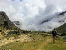 Άτομο που περπατά στα σύννεφα υψηλά στα βουνά των Άνδεων κατά μήκος του θορίου στοκ εικόνα