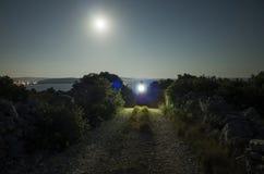 Άτομο που περπατά στο δρόμο με το φως λάμψης τη νύχτα κάτω από το φεγγάρι στοκ φωτογραφία με δικαίωμα ελεύθερης χρήσης