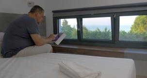 Άτομο που περπατά στο δωμάτιο και που κάθεται στο κρεβάτι χρησιμοποίηση ταμπλετών απόθεμα βίντεο