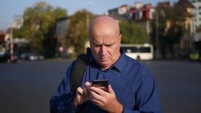 Άτομο που περπατούν στην οδό σε στο κέντρο της πόλης και κείμενο που χρησιμοποιούν το τηλέφωνο κυττάρων φιλμ μικρού μήκους