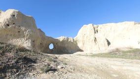 Άτομο που πηγαίνει στην πυίδα τρύπα σε έναν σχηματισμό βράχου σπηλιών απόθεμα βίντεο