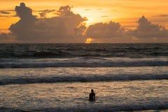 Άτομο που πηγαίνει στη θάλασσα κατά τη διάρκεια του ηλιοβασιλέματος Στοκ Εικόνες