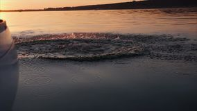 Άτομο που πηδά από το γιοτ στον ποταμό στο ηλιοβασίλεμα απόθεμα βίντεο