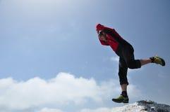 Άτομο που πηδά από έναν απότομο βράχο Στοκ Εικόνα