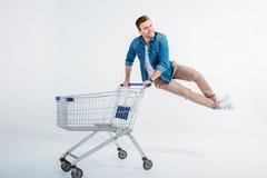 Άτομο που πηδά και που έχει τη διασκέδαση με το καροτσάκι αγορών στο λευκό Στοκ φωτογραφία με δικαίωμα ελεύθερης χρήσης