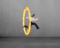 Άτομο που πηδά μέσω της στεφάνης πυρκαγιάς με το συμπαγή τοίχο στοκ εικόνα με δικαίωμα ελεύθερης χρήσης
