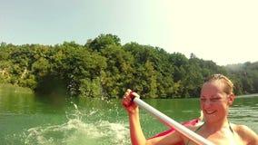 Άτομο που πηδά στο νερό από το κανό ενώ η φίλη του που γελά σε ένα κανό απόθεμα βίντεο