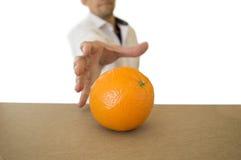 Άτομο που πιάνει ένα πορτοκάλι Στοκ φωτογραφία με δικαίωμα ελεύθερης χρήσης
