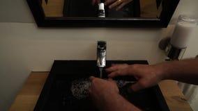Άτομο που πλένει τα χέρια τους στο νεροχύτη στο λουτρό φιλμ μικρού μήκους
