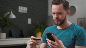 Άτομο που πληρώνει με την πιστωτική κάρτα στο έξυπνο τηλέφωνο στο σπίτι Καυκάσιος τύπος που χρησιμοποιεί το smartphone για on-lin απόθεμα βίντεο