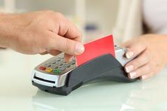 Άτομο που πληρώνει με τον αναγνώστη πιστωτικών καρτών σε ένα κατάστημα Στοκ φωτογραφία με δικαίωμα ελεύθερης χρήσης
