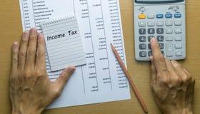 Άτομο που προγραμματίζει το μηνιαίο φόρο εισοδήματος Στοκ φωτογραφία με δικαίωμα ελεύθερης χρήσης