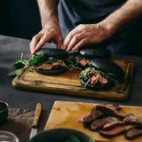 Άτομο που προετοιμάζει τα μαύρα burgers με το ψημένο στη σχάρα κρέας βόειου κρέατος Στοκ φωτογραφίες με δικαίωμα ελεύθερης χρήσης