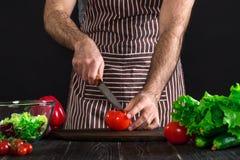 Άτομο που προετοιμάζει τη σαλάτα σε έναν ξύλινο πίνακα Τα χέρια ατόμων ` s κόβουν την ντομάτα για να κάνουν μια σαλάτα στο μαύρο  Στοκ εικόνες με δικαίωμα ελεύθερης χρήσης