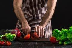 Άτομο που προετοιμάζει τη σαλάτα σε έναν ξύλινο πίνακα Τα χέρια ατόμων ` s κόβουν την ντομάτα για να κάνουν μια σαλάτα στο μαύρο  Στοκ εικόνα με δικαίωμα ελεύθερης χρήσης