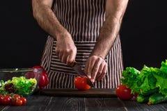 Άτομο που προετοιμάζει τη σαλάτα σε έναν ξύλινο πίνακα Τα χέρια ατόμων ` s κόβουν την ντομάτα για να κάνουν μια σαλάτα στο μαύρο  Στοκ Εικόνες