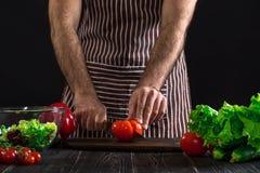 Άτομο που προετοιμάζει τη σαλάτα σε έναν ξύλινο πίνακα Τα χέρια ατόμων ` s κόβουν την ντομάτα για να κάνουν μια σαλάτα στο μαύρο  Στοκ Εικόνα