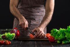 Άτομο που προετοιμάζει τη σαλάτα σε έναν ξύλινο πίνακα Τα χέρια ατόμων ` s κόβουν την ντομάτα για να κάνουν μια σαλάτα στο μαύρο  Στοκ Φωτογραφία