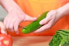 Άτομο που προετοιμάζει το αγγούρι αποφλοίωσης σαλάτας λαχανικών Στοκ Φωτογραφίες