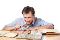 Άτομο που προσέχει μια συλλογή των γραμματοσήμων με πιό magnifier Στοκ Εικόνες
