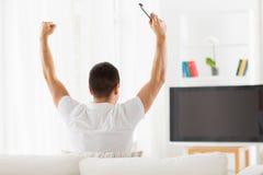Άτομο που προσέχει τη TV και που υποστηρίζει την ομάδα στο σπίτι Στοκ φωτογραφία με δικαίωμα ελεύθερης χρήσης