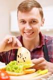 Άτομο που προσθέτει το τυρί στο σάντουιτς Στοκ Εικόνες