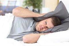 Άτομο που προσπαθεί στον ύπνο που καλύπτει τα αυτιά για το θόρυβο Στοκ Φωτογραφία