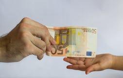 Άτομο που προσφέρει τα χρήματα σε ένα παιδί Χρήματα στα χέρια στοκ φωτογραφία με δικαίωμα ελεύθερης χρήσης