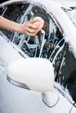 Άτομο που πλένει το άσπρο αυτοκίνητο με το σφουγγάρι Στοκ Εικόνα