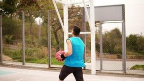 Άτομο που ρίχνει τη σφαίρα καλαθοσφαίρισης στο δικαστήριο στο πάρκο, σε αργή κίνηση πυροβολισμός φιλμ μικρού μήκους