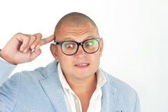 Άτομο που σκέφτεται ένα ανόητο πρόσωπο με τα γυαλιά nerd που απομονώνεται κάνοντας στο λευκό Στοκ φωτογραφία με δικαίωμα ελεύθερης χρήσης