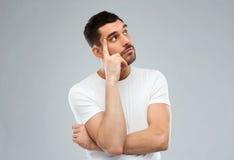 Άτομο που σκέφτεται πέρα από το γκρίζο υπόβαθρο Στοκ εικόνα με δικαίωμα ελεύθερης χρήσης