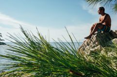 Άτομο που σκέφτεται στον απότομο βράχο στοκ εικόνα με δικαίωμα ελεύθερης χρήσης
