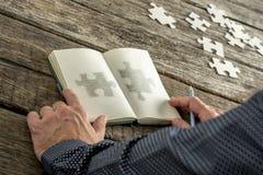 Άτομο που σκιαγραφεί δύο κομμάτια γρίφων matchng στο σημειωματάριό του Στοκ Φωτογραφία