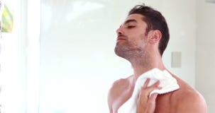 Άτομο που σκουπίζει το πρόσωπό του μπροστά από τον καθρέφτη φιλμ μικρού μήκους