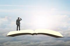 Άτομο που στέκεται και που κοιτάζει στο βιβλίο που πετά στον ουρανό Στοκ φωτογραφία με δικαίωμα ελεύθερης χρήσης