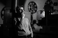 Άτομο που στέκεται κοντά σε έναν προβολέα ταινιών στο μηχανικό προβολής δωματίων Στοκ Εικόνες