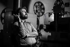 Άτομο που στέκεται κοντά σε έναν προβολέα ταινιών στο μηχανικό προβολής δωματίων Στοκ φωτογραφία με δικαίωμα ελεύθερης χρήσης