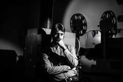 Άτομο που στέκεται κοντά σε έναν προβολέα ταινιών στο μηχανικό προβολής δωματίων Στοκ Φωτογραφίες