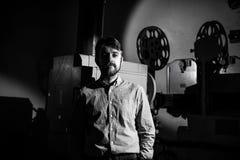Άτομο που στέκεται κοντά σε έναν προβολέα ταινιών στο μηχανικό προβολής δωματίων Στοκ εικόνα με δικαίωμα ελεύθερης χρήσης